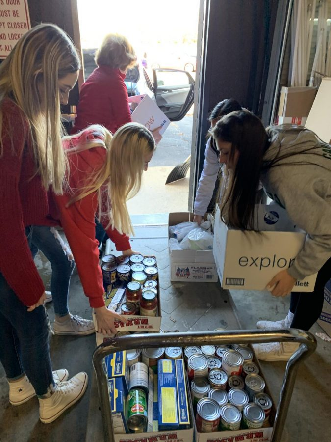 Key Club members loading cars up with boxes of food